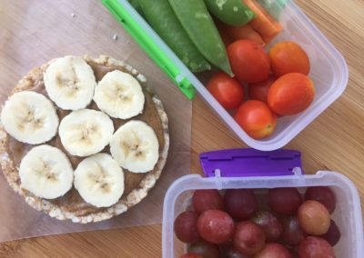 Cinnamon brown rice cake with almond butter and bananas, veggie mix and grapes