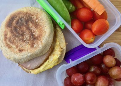 Breakfast sandwich with veggies and grapes